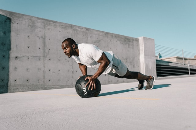 Man doing incline push ups on exercise ball