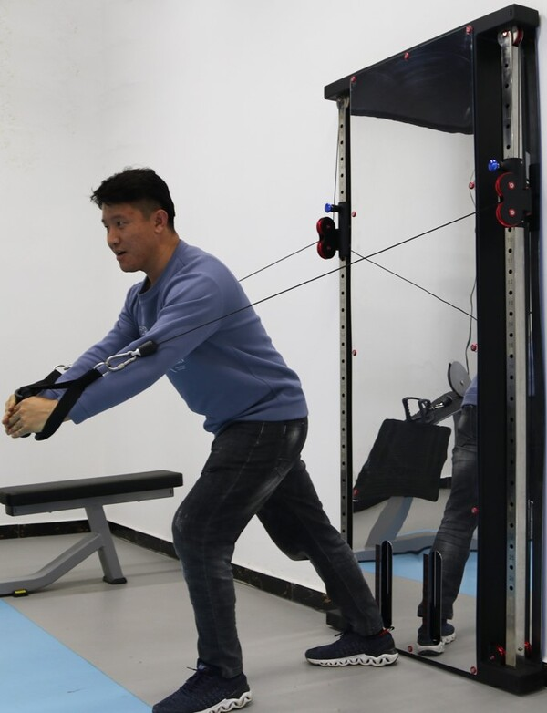 Man showing cable reach of functional trainer