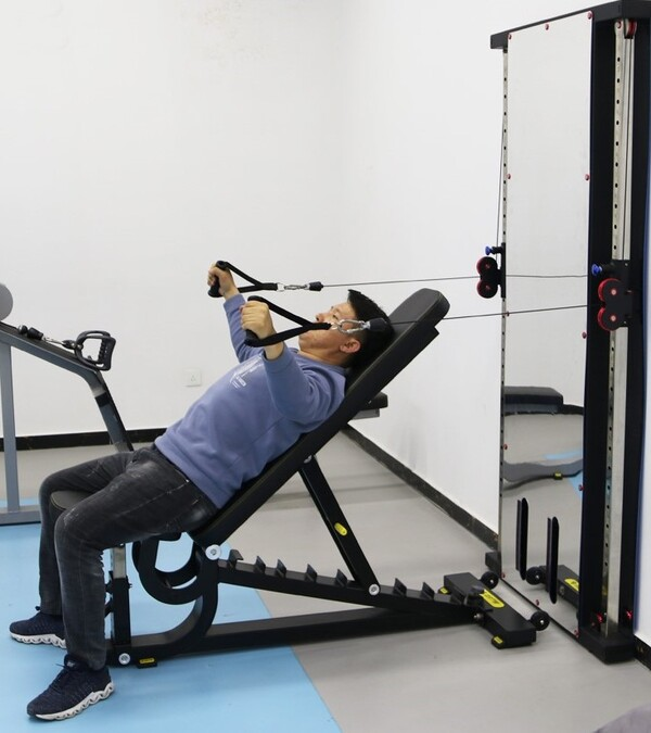 Man on weight bench in front of wall mounted functional trainer mirror
